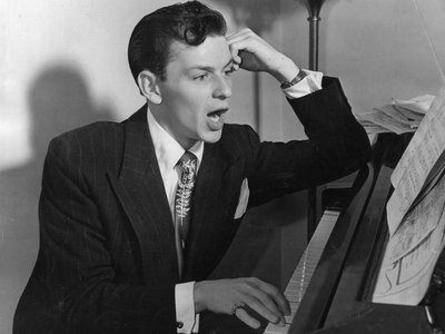American singer and actor Frank Sinatra sits at the piano. Getty Images